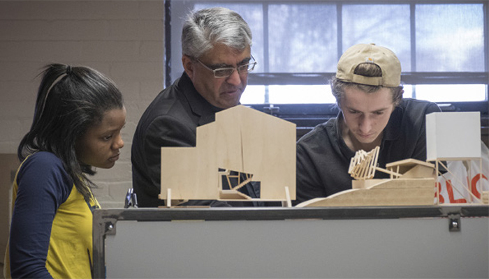 A Detroit Mercy professor and two students look at an architecture project.
